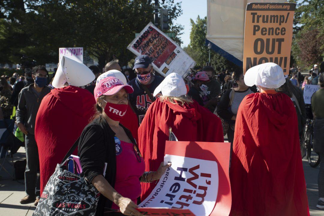 A Trump supporter walks behind the handmaidens.